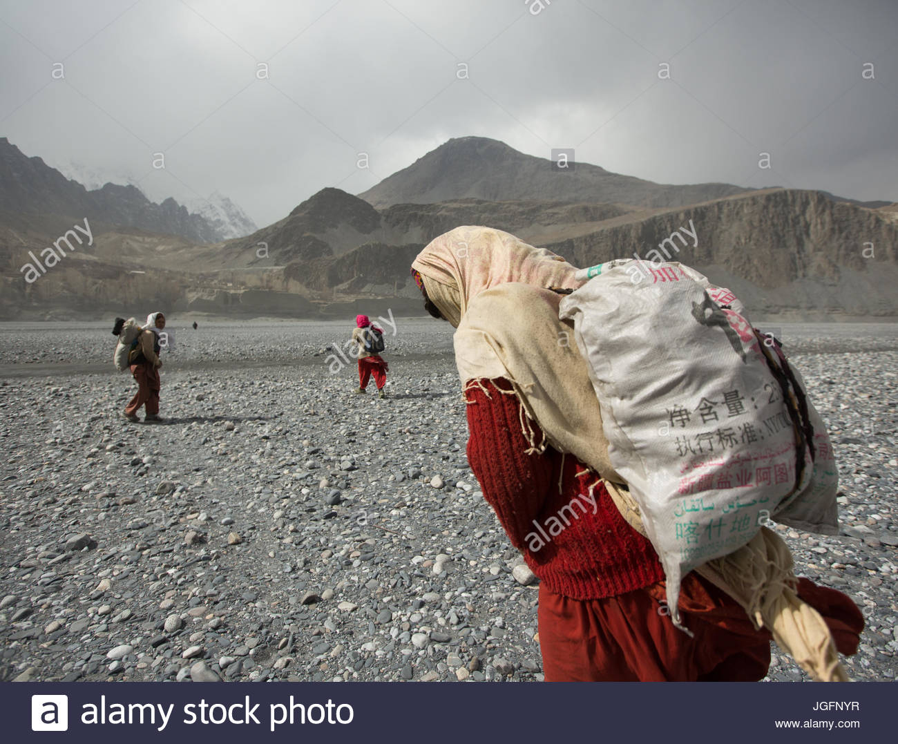 Women carry potatoes in sack, a two hour trek each way from the field. Stock Photo
