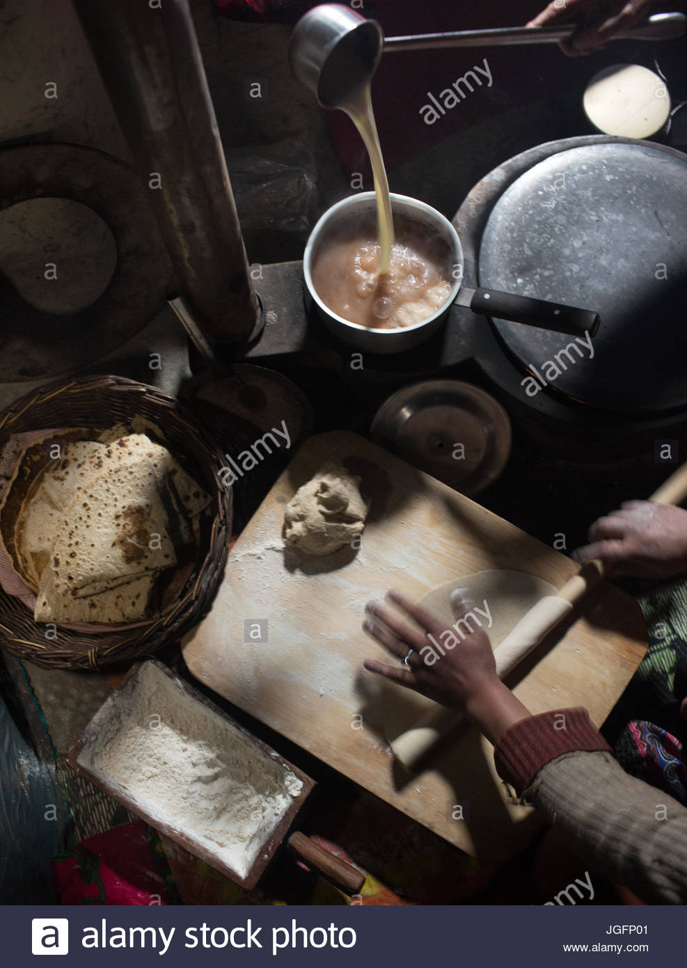 Cooking chalpindok, chapatis with dried yak milk sauce, in a home in the Hunza Region. - Stock Image