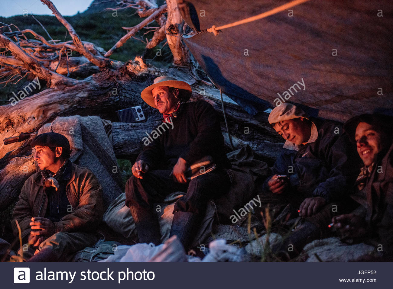 Gauchos, or cowboys, gather around a fire to eat sandwiches and meat and drink wine before going to sleep. - Stock Image