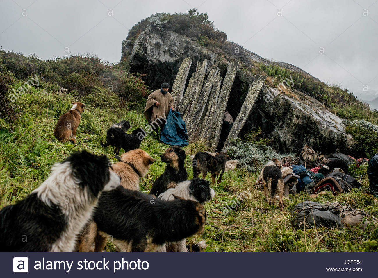 Gauchos find an old shelter under a boulder to spend the night on the way to Sutherland, in Peninsula Antonio Varas. - Stock Image