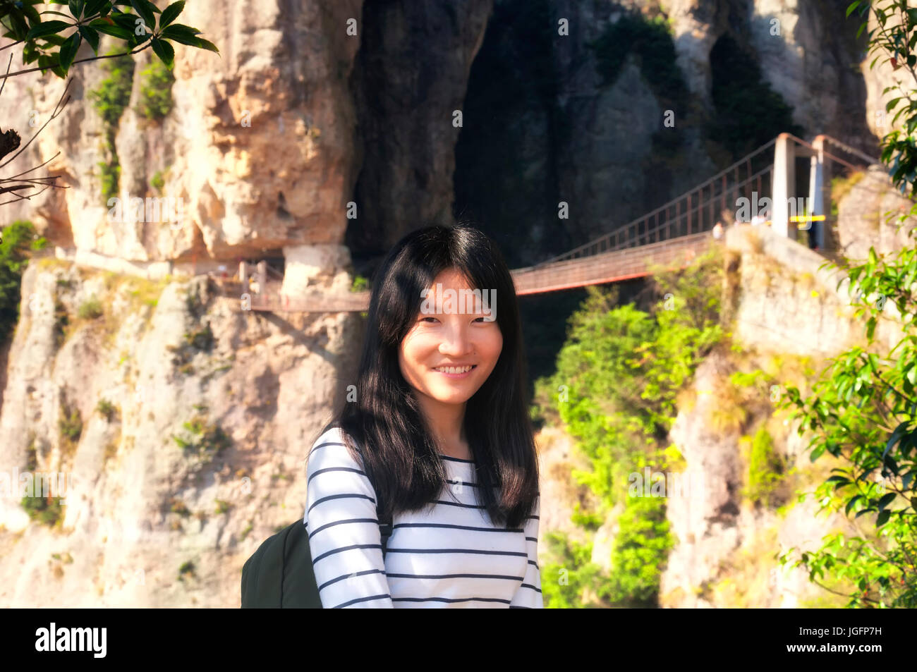 A chinese woman smiling with the Fangdong suspension bridge spanning a sheer cliff in the background in the yandangshan - Stock Image