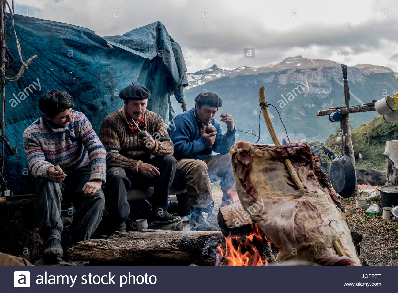 Bagualeros, or cowboys who capture feral livestock, barbecue meat from a feral animal and drink mate tea. - Stock Image