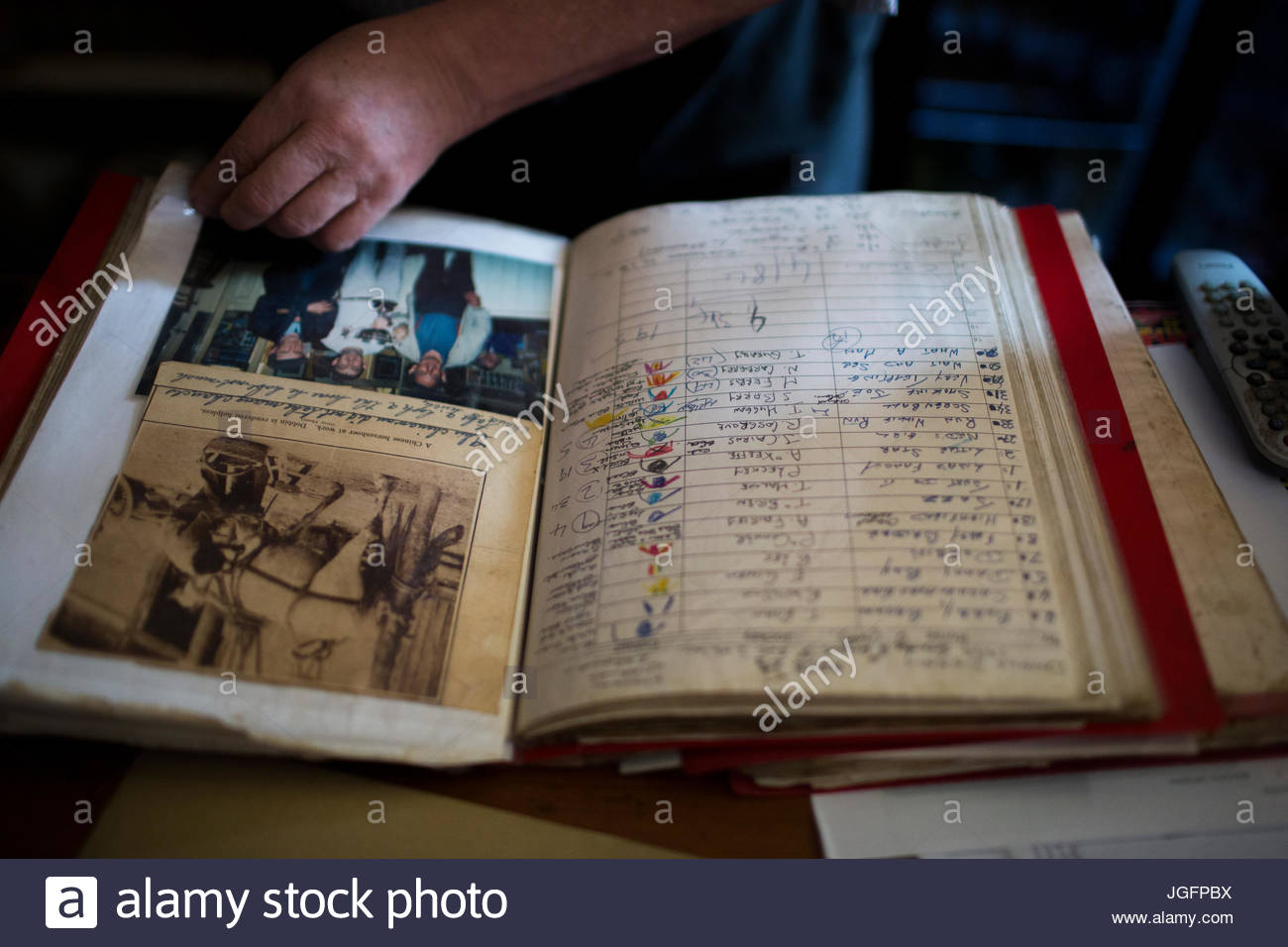 Inside the J. Curran pub in Dingle, the owner leafs through an old ledger containing mementos from Irish emigrants. - Stock Image