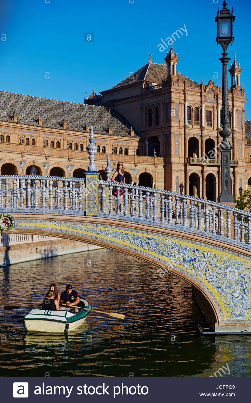 Boaters float under a tiled bridge near the 1920s complex known as Plaza de Espana. - Stock Image