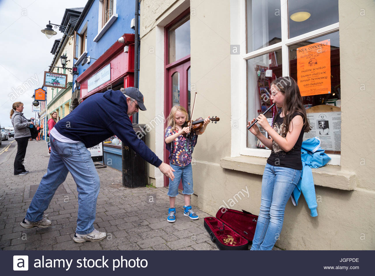 Girls play music on the street in Longford to earn ice cream money. - Stock Image