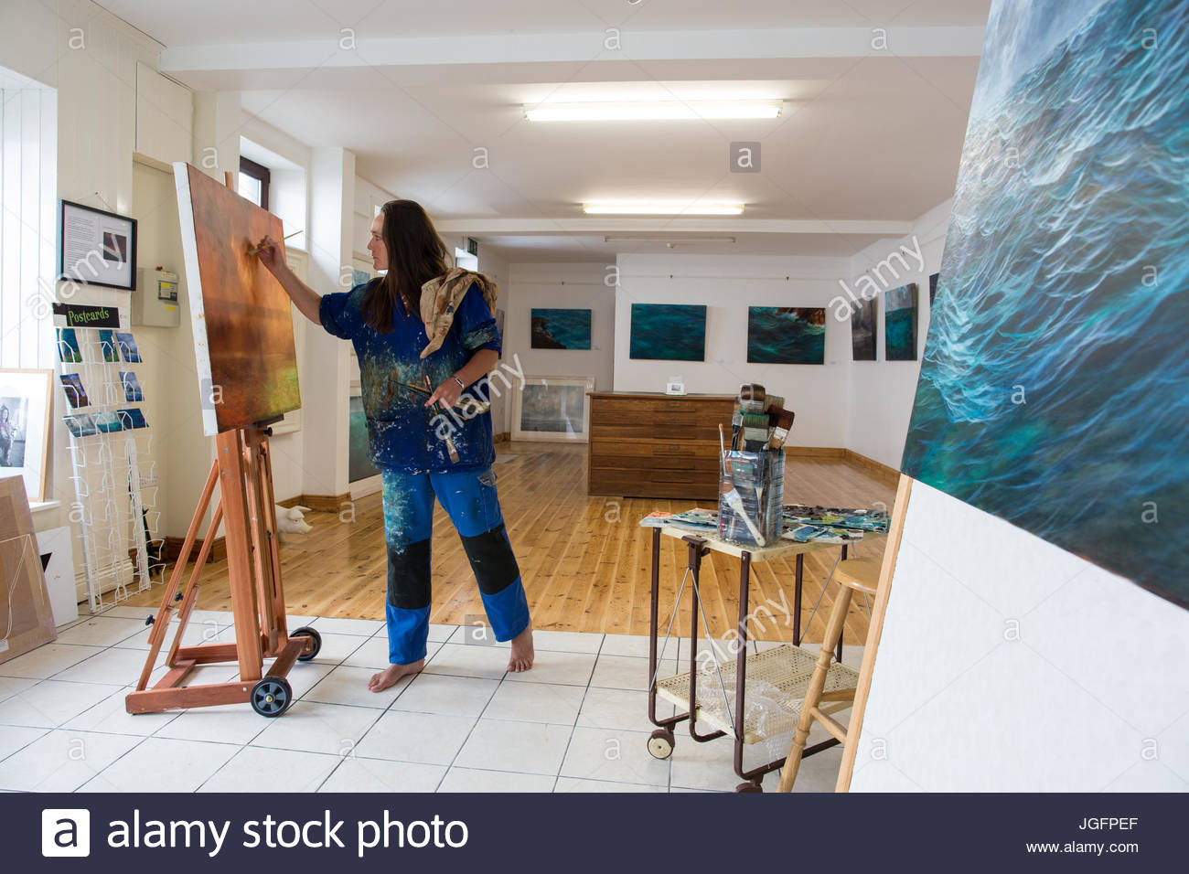 Artist Carol Cronin paints the waterscapes of Ireland in her Dingle studio. - Stock Image