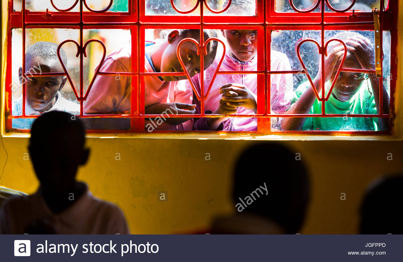 Children gaze through the windows of a school they are unable to attend. - Stock Image