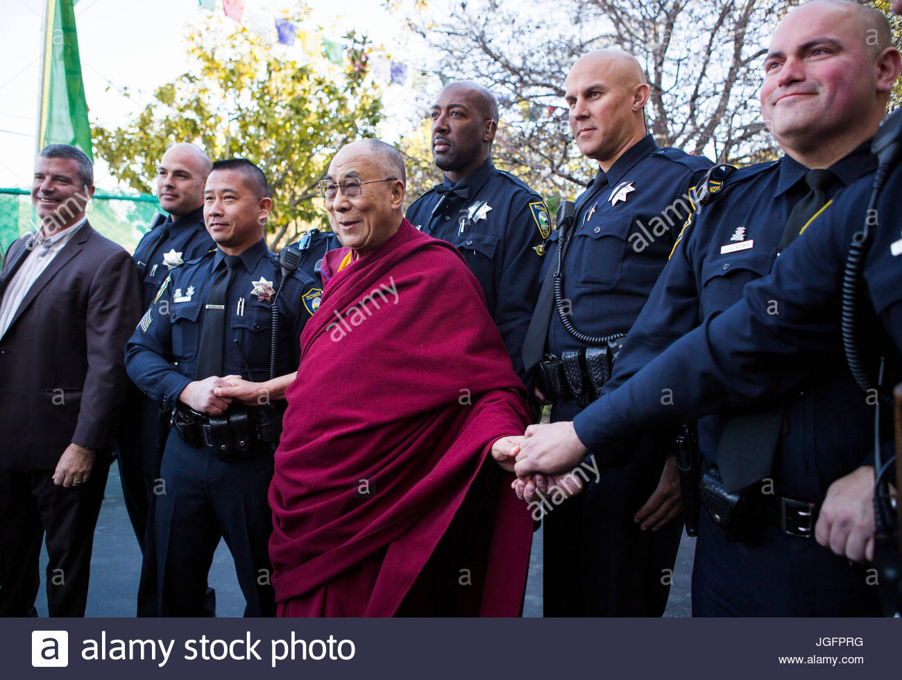 The Dalai Lama joins hands with law enforcement officers. - Stock Image