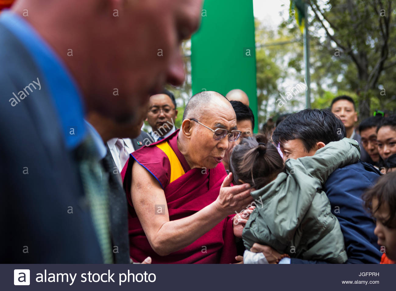 The Dalai Lama leans down to greet a child. - Stock Image