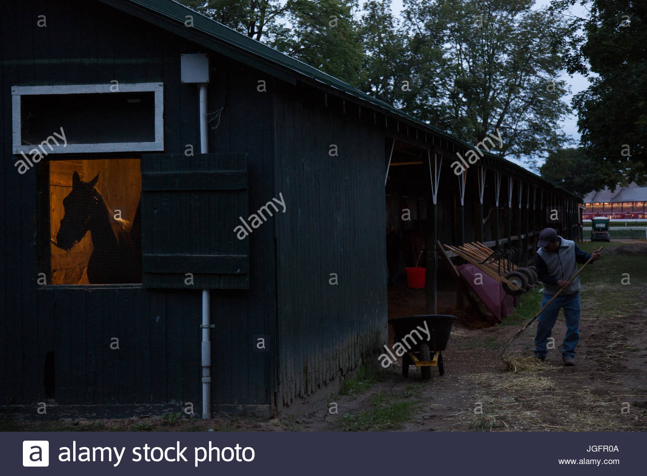 A groom mucks out the stables in the early morning. - Stock Image