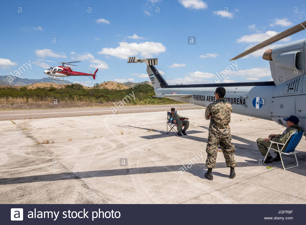 A Honduran military helicopter awaits a repair as an American chopper returns from taking members of an expedition - Stock Image