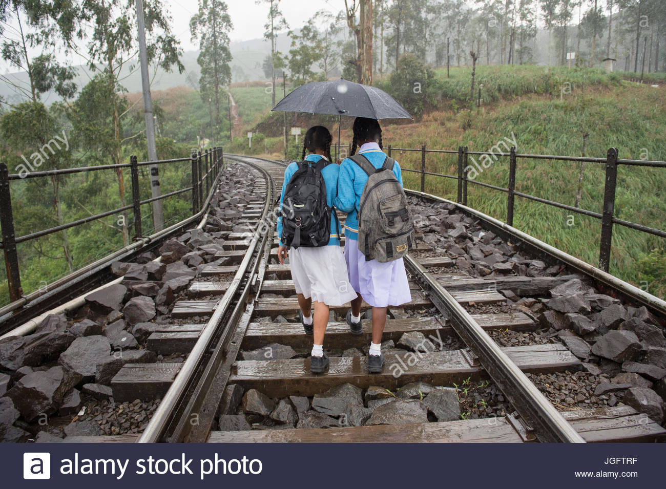 Students walk home after school to their nearby village, walking along the railway tracks in the rain from Nano - Stock Image