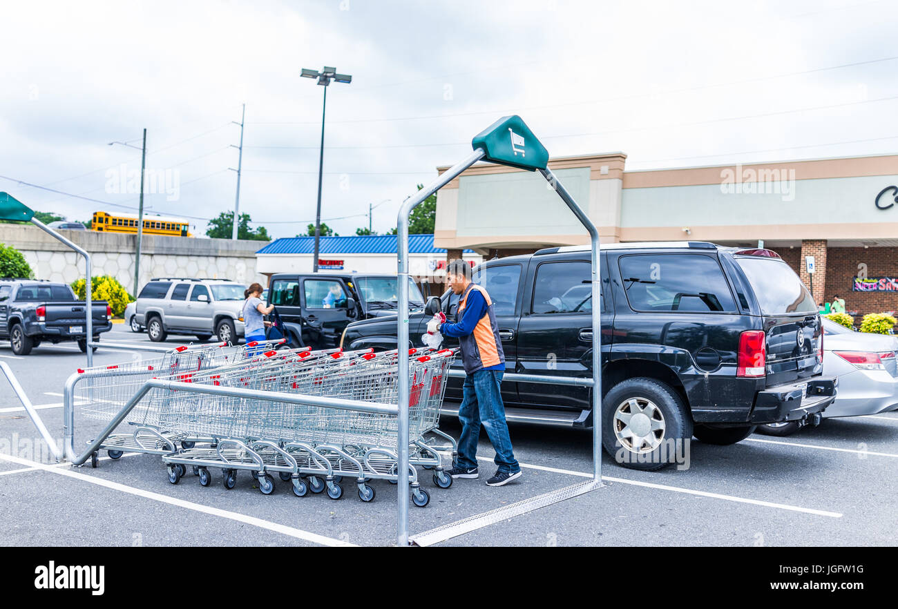 Burke, USA - June 16, 2017: Hmart shopping carts with man worker organzing them - Stock Image
