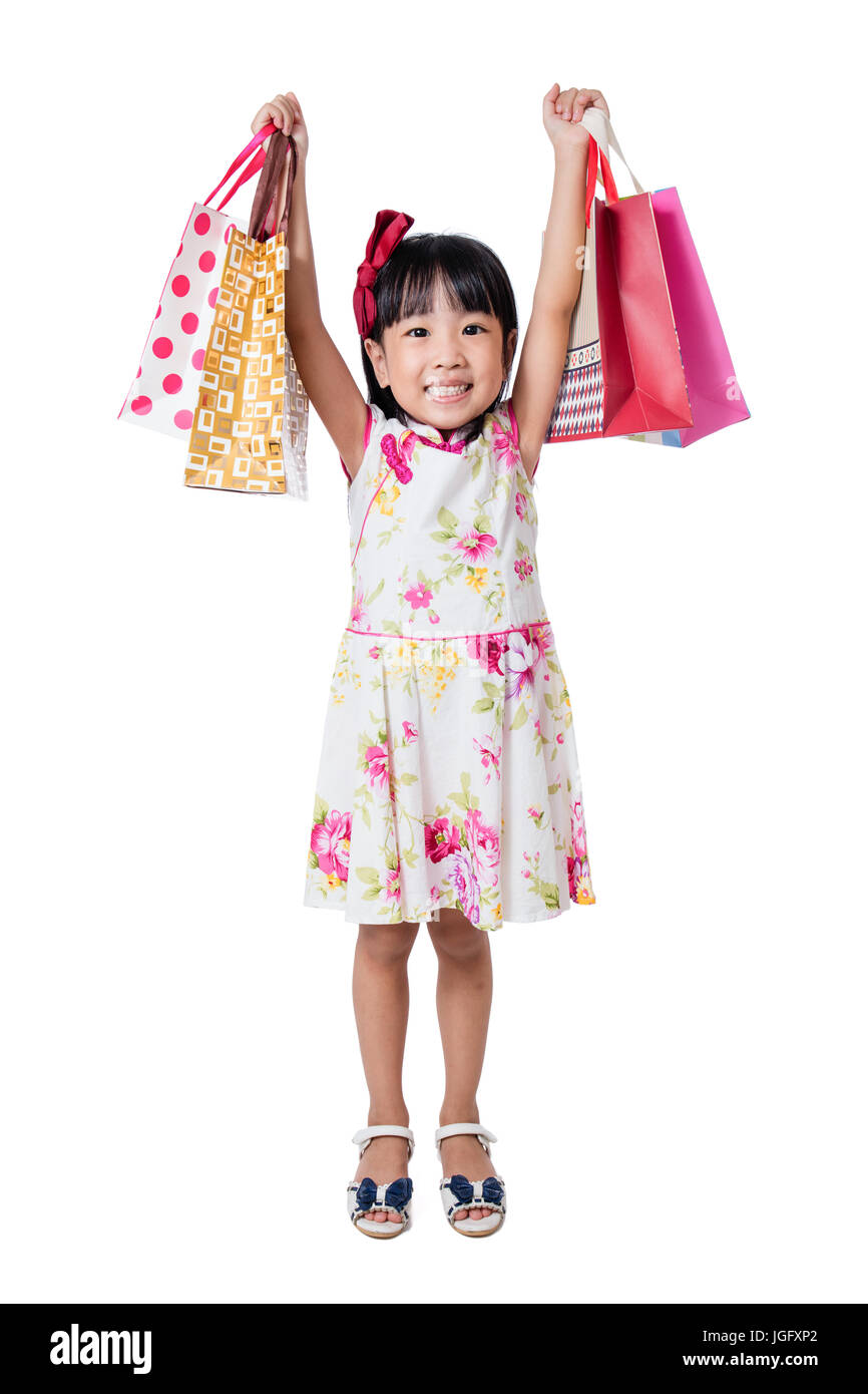 6fd099ccd Asian Chinese little girl wearing cheongsam holding shopping bags in  isolated white background