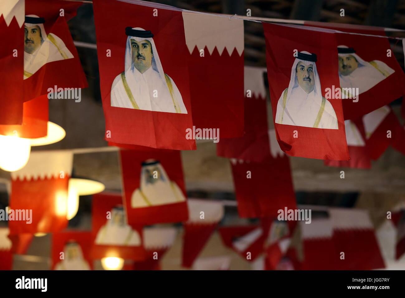 DOHA, QATAR - JULY 6, 2017: Ntional flags printed with images of Qatari Emir Sheikh Tamim bin Hamad al-Thani are Stock Photo