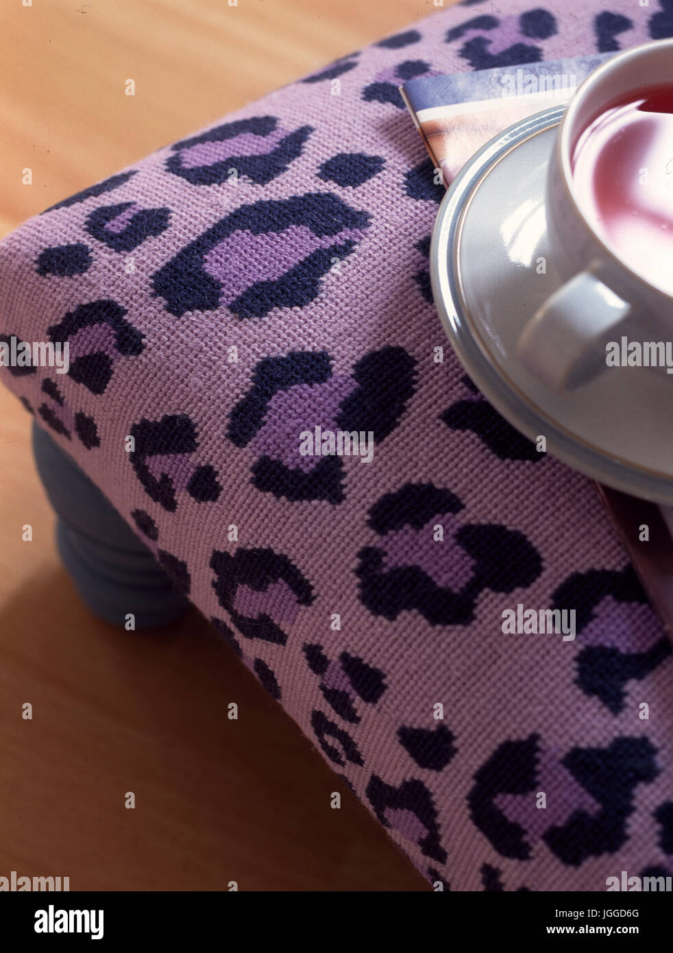Detail of cup of tea on mauve needlepoint footstool - Stock Image