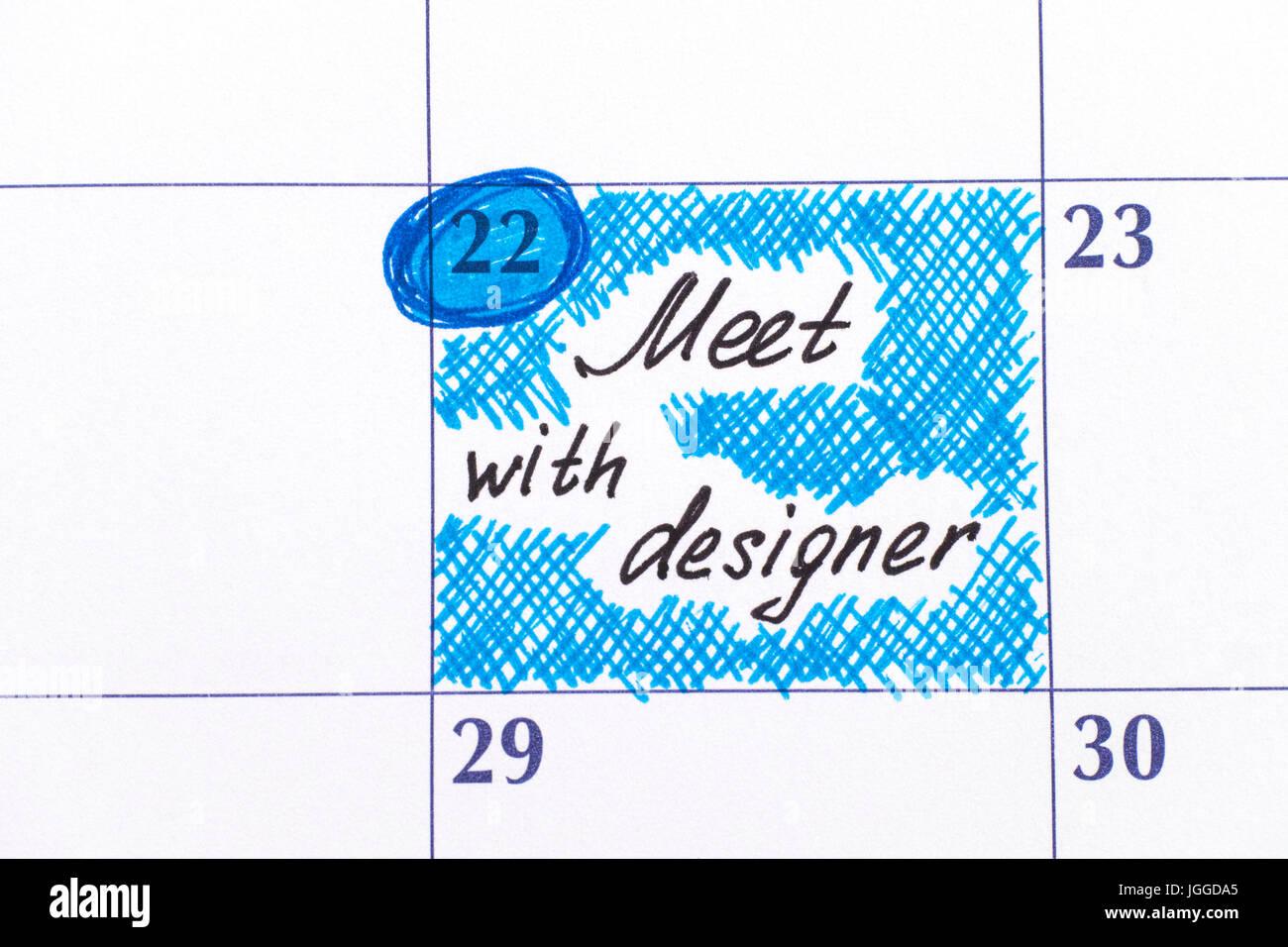 Reminder Meet with designer in calendar. Close-up. - Stock Image