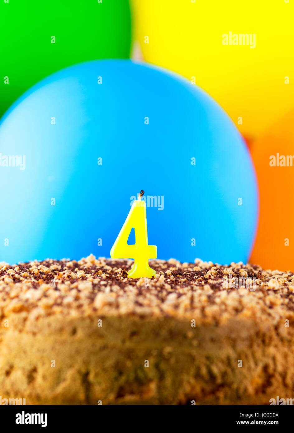Homemade cake with number four candle and balloons background. - Stock Image