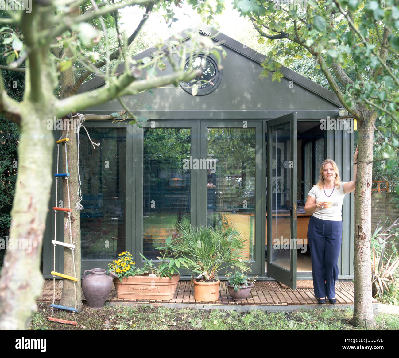 home office in the garden. Woman Standing Beside Garden Home Office In The