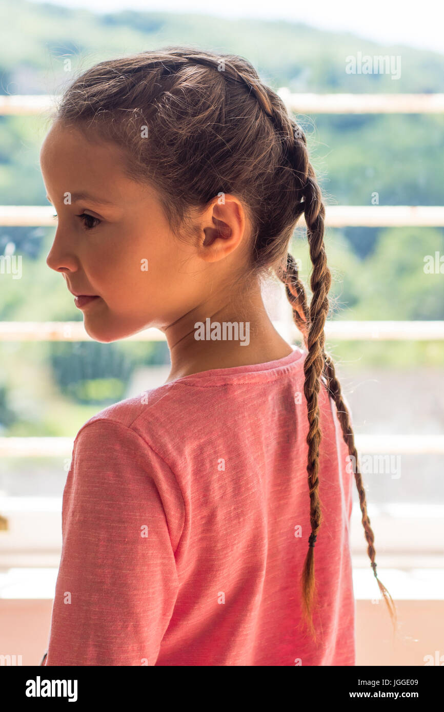 Girl with Dutch plaits looking out of window in profile. Young child with brown hair braided in a pink top - Stock Image