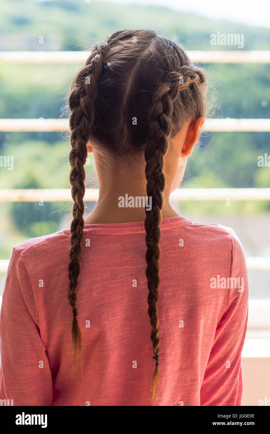 Girl with Dutch plaits looking out of window from behind. Young child with brown hair braided in a pink top - Stock Image