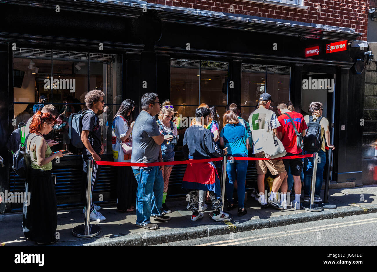 Queue of young people waiting outside trendy shop Supreme on Peter Street, Soho, London, England, UK. - Stock Image