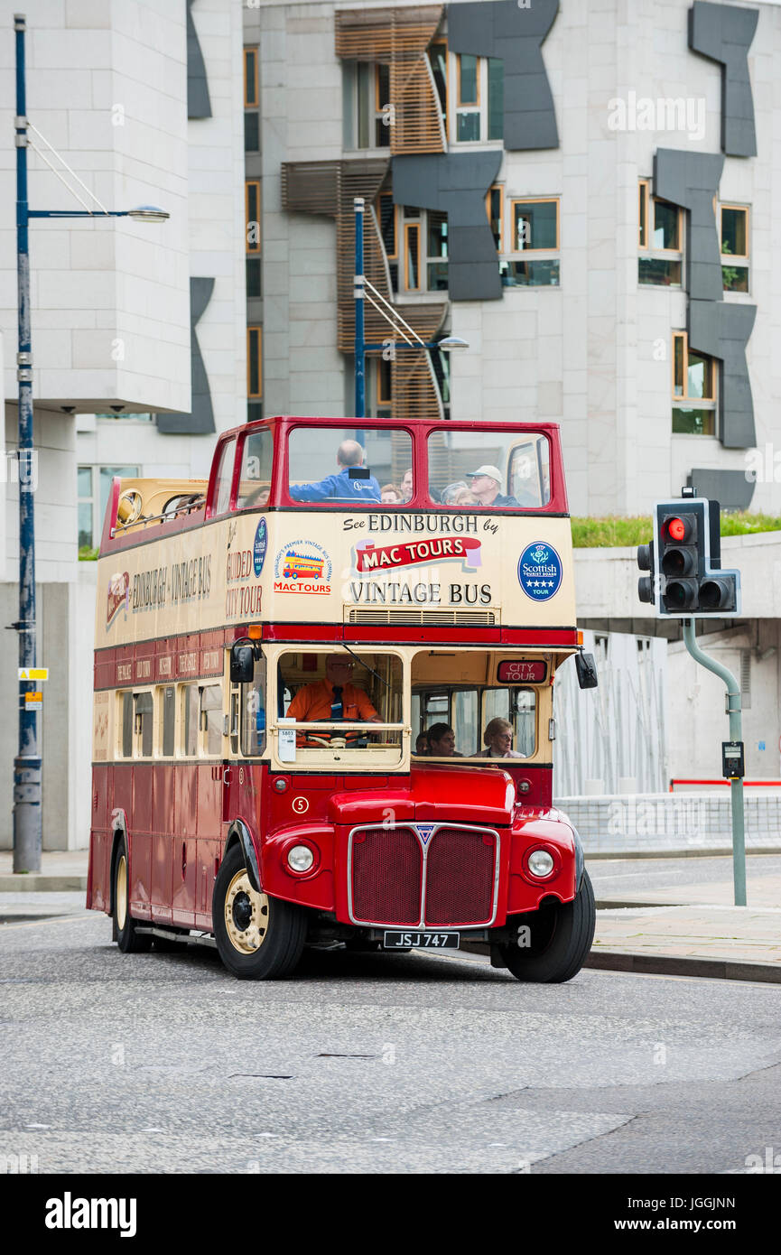 Edinburgh, Scotland, UK - July 19, 2011: A vintage tour bus with the Scottish Parliament in the background. - Stock Image