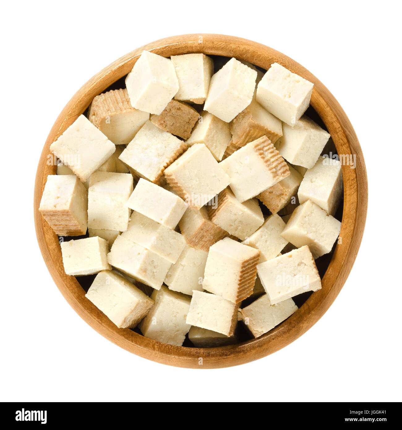 Smoked tofu cubes in wooden bowl. Bean curd. Coagulated soy milk, pressed into firm white blocks. Component of Asian - Stock Image