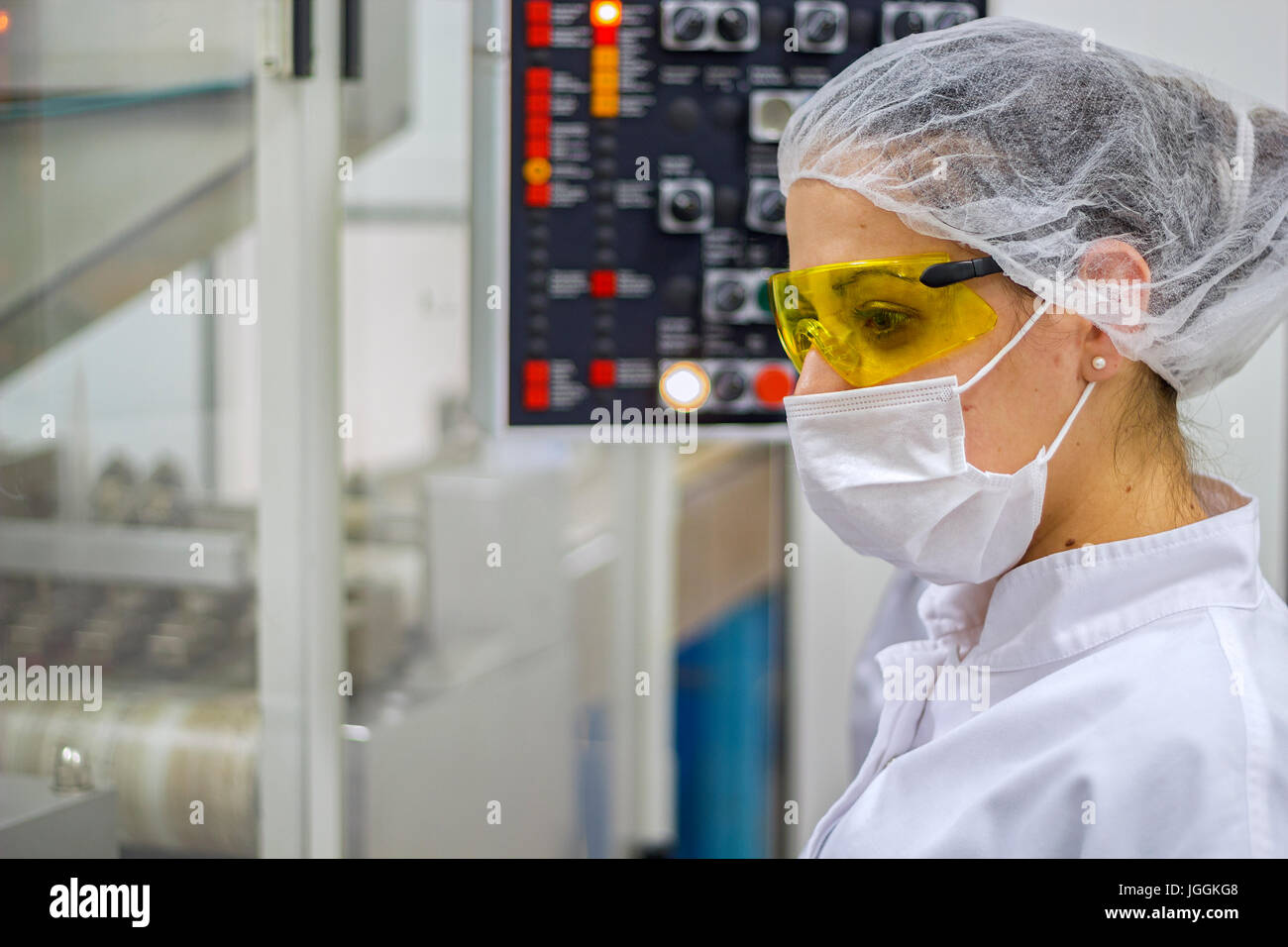Pharmaceutical technician using the control panel of pill packaging machine.  Pharmaceutical industry. - Stock Image