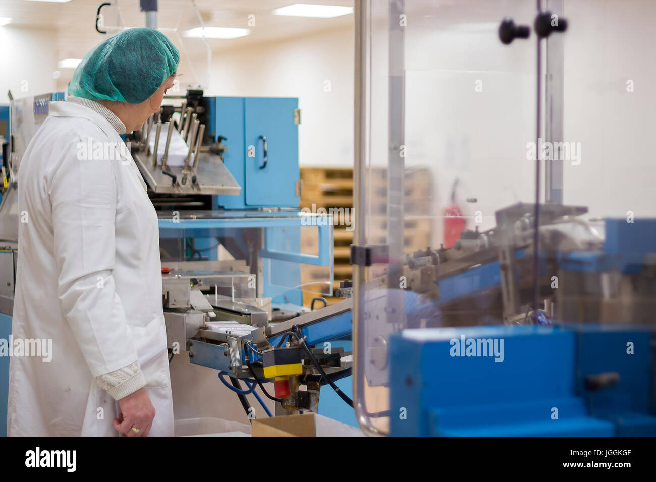 Pharmaceutical female worker controlling the medical pill packaging line. - Stock Image