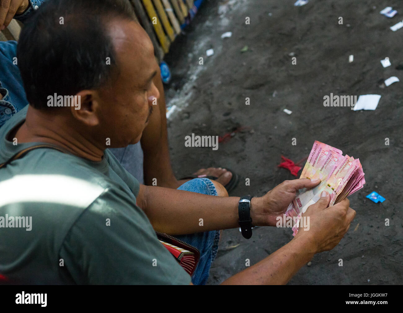Men taking the money for the bets during a cockfigting event, Bali island, Canggu, Indonesia - Stock Image
