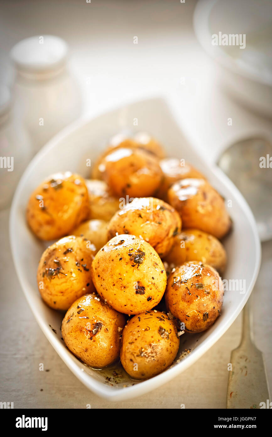 Baby jacket potatoes with herb and garlic oil dressing - Stock Image