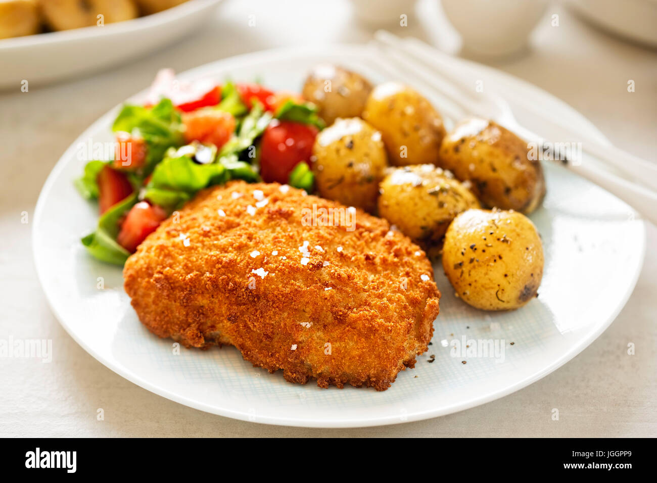 Traditional breaded fillet of cod with baby potatoes and salad - Stock Image