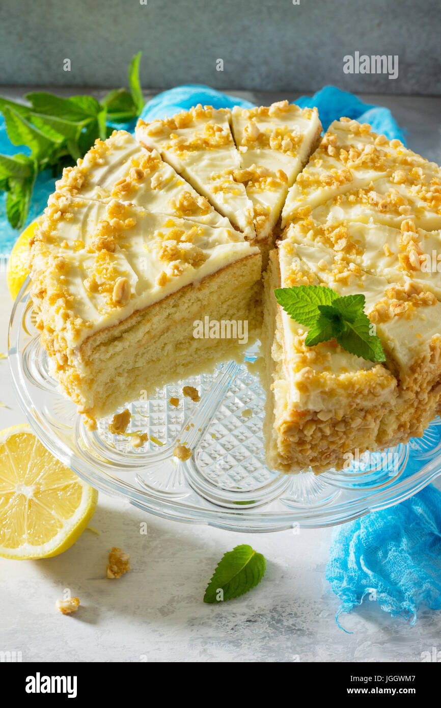 Delicious birthday cake lemon biscuit and butter cream, walnut roasted. Serving of a festive table. - Stock Image