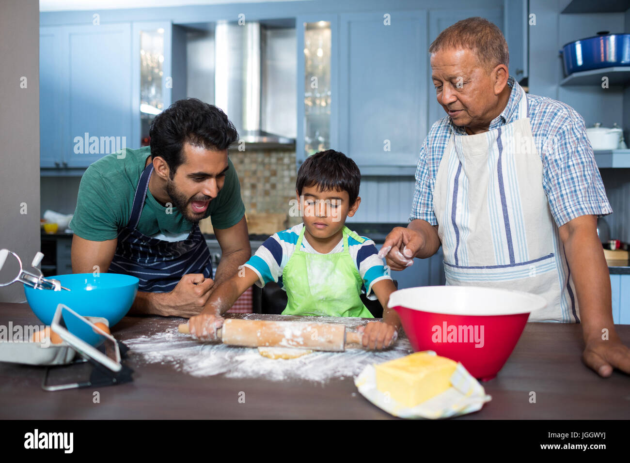 Father shouting with son rolling dough while standing by grandfather ...
