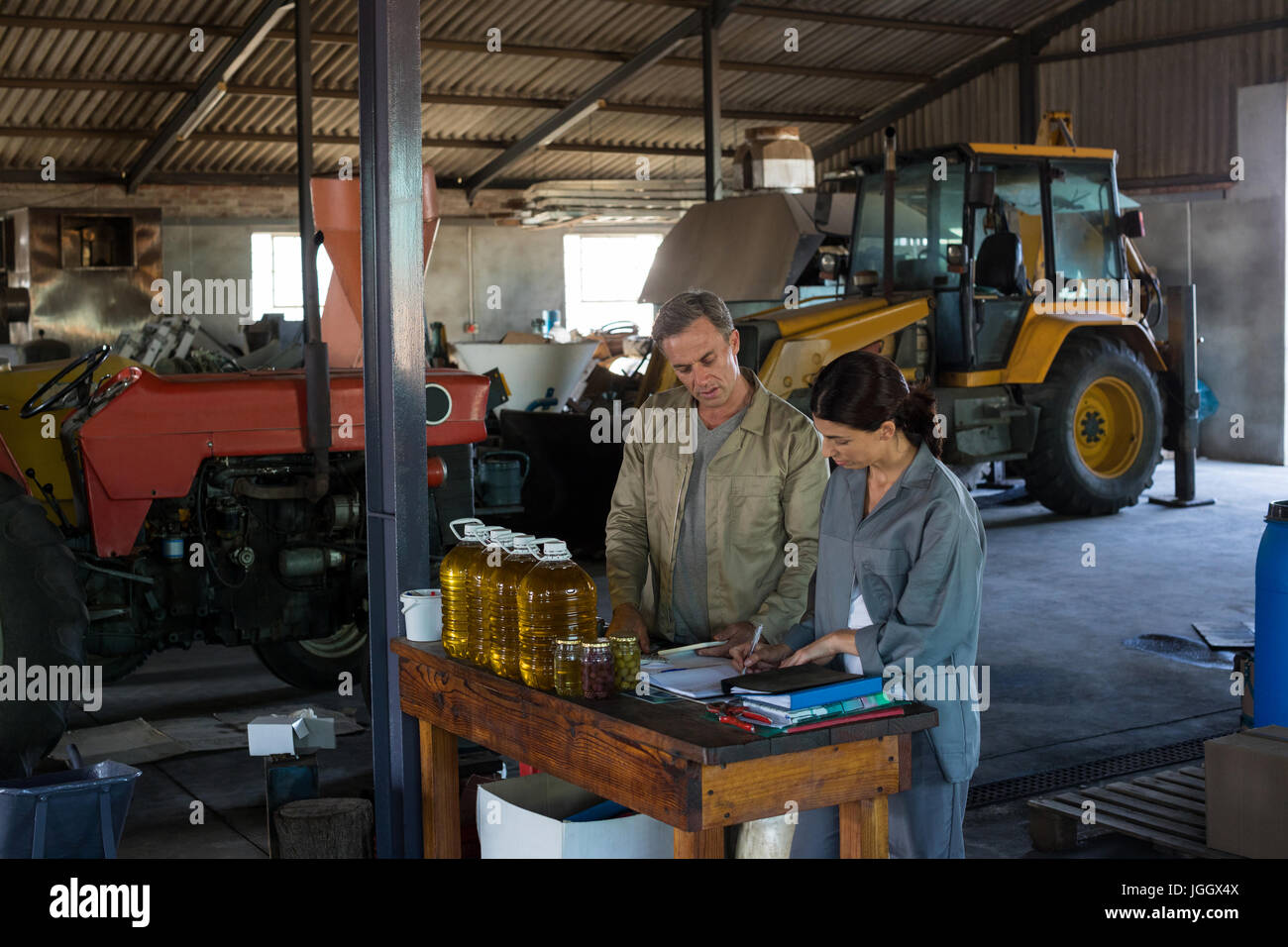 Workers maintaining record in book at olive factory - Stock Image