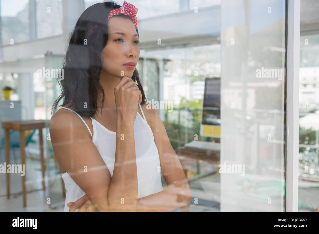Thoughtful businesswoman looking through window seen through glass - Stock Image