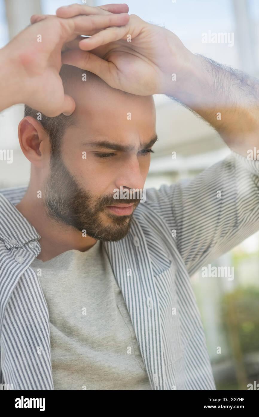 Thoughtful designer looking through window at studio seen through glass - Stock Image