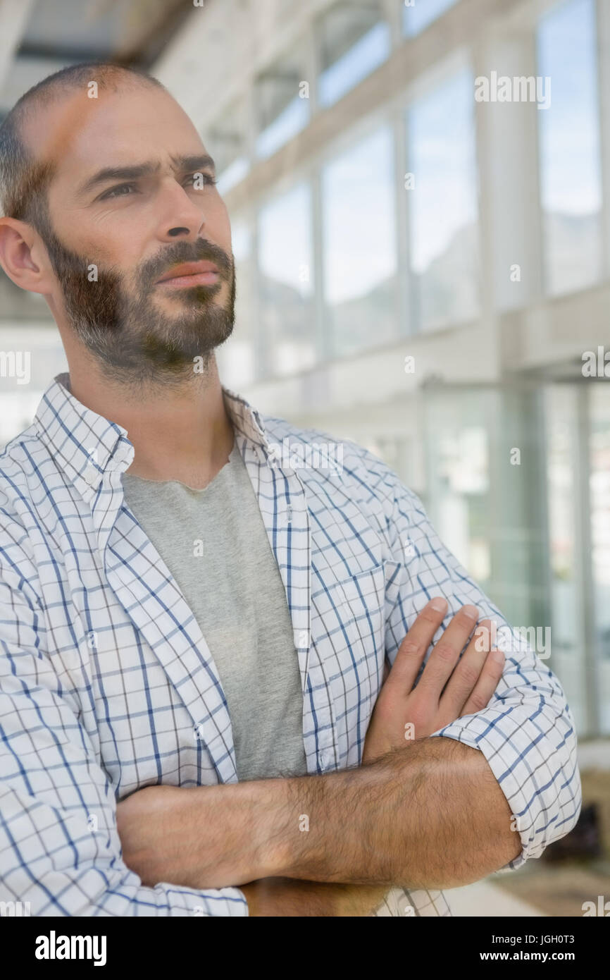 Thoughtful male designer with arms crossed looking through window seen through glass - Stock Image