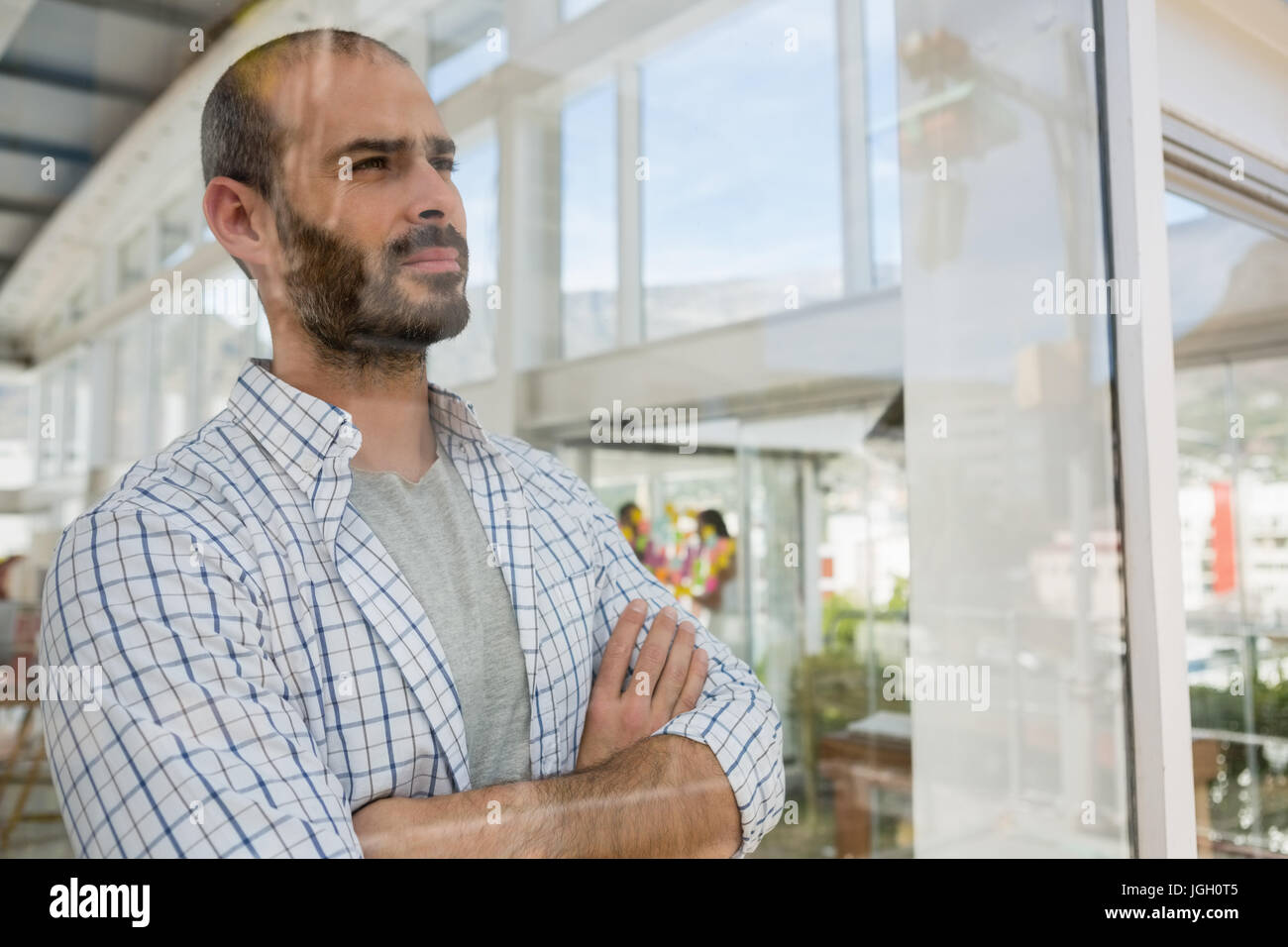 Thoughtful designer with arms crossed looking through window seen through glass - Stock Image
