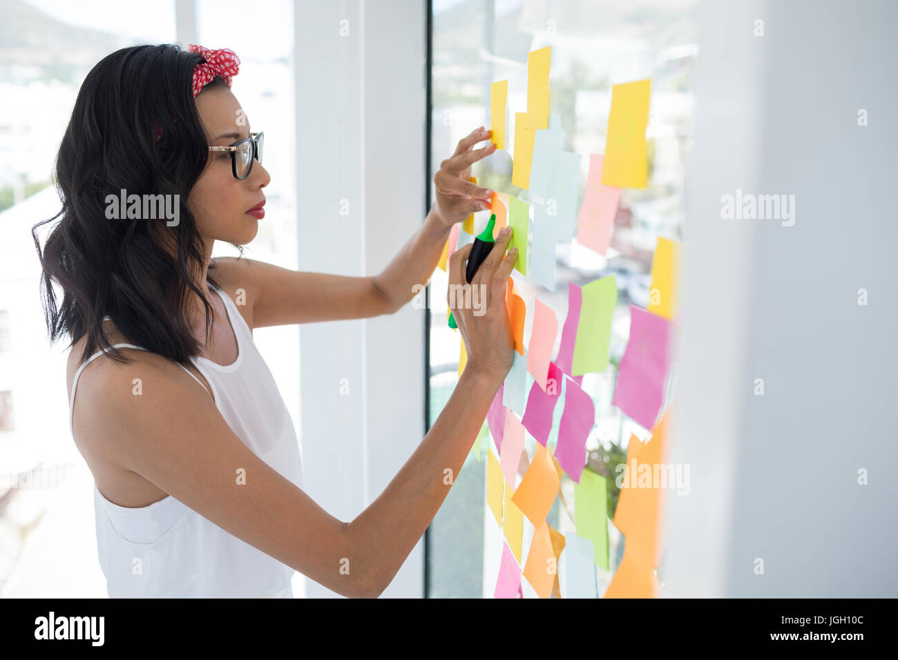 Female executive writing on sticky notes in office - Stock Image