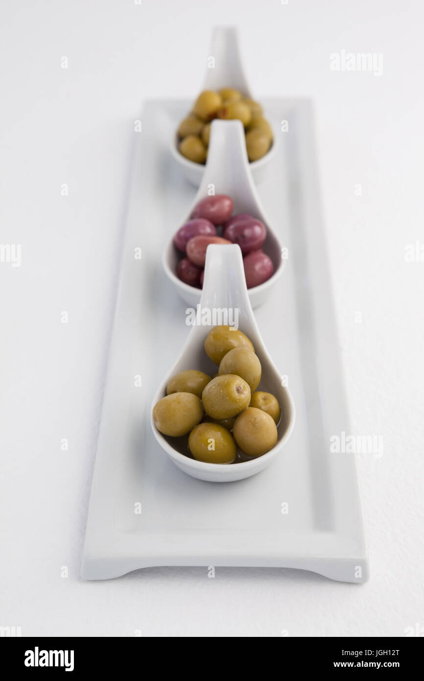 High angle view of green and black olives in containers on tray against white background - Stock Image