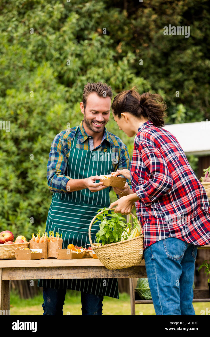 Young man selling organic vegetables to woman at farm Stock Photo