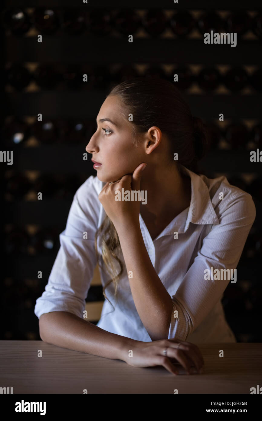 Thoughtful woman sitting at counter in bar - Stock Image
