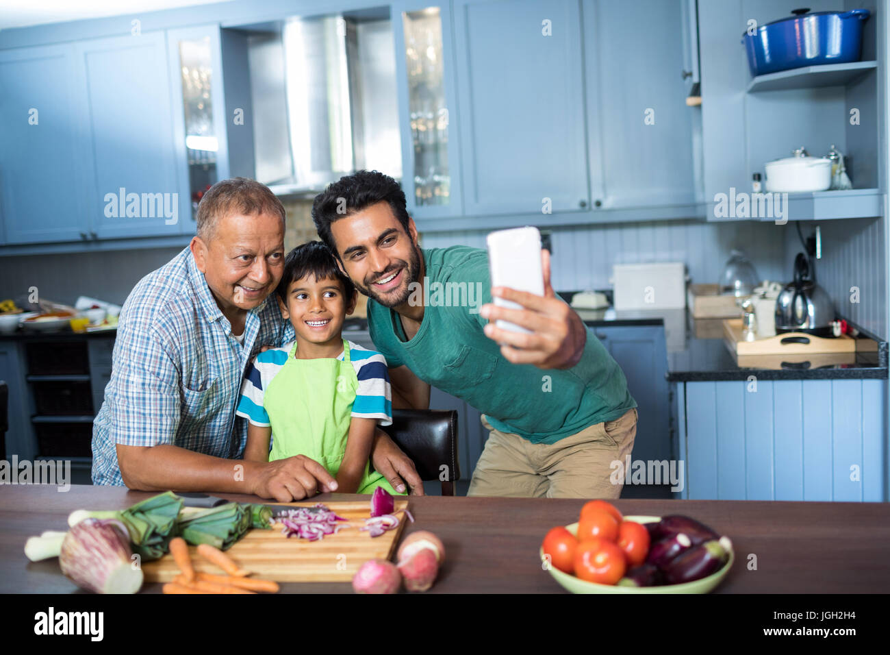 Family taking selfie while preparing food in kitchen at home Stock ...