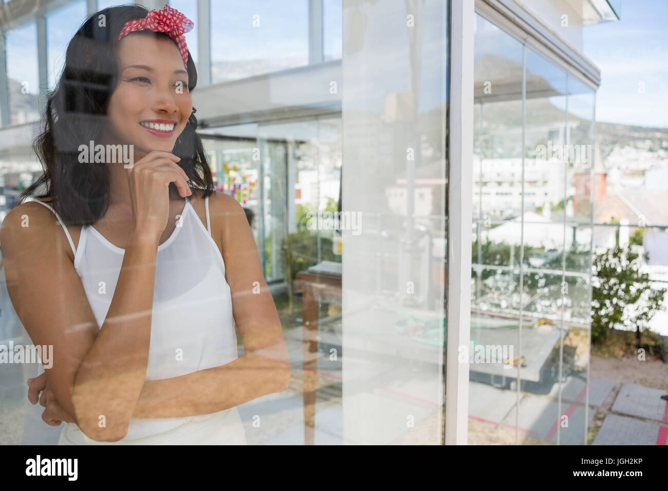 Smiling thoughtful businesswoman looking through window seen through glass - Stock Image