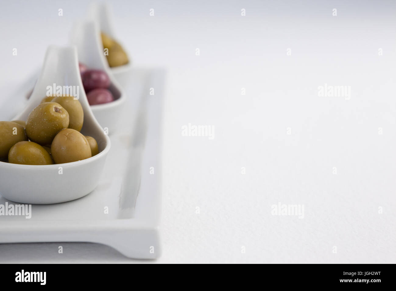 Close up of black and green olives in containers on tray against white background - Stock Image