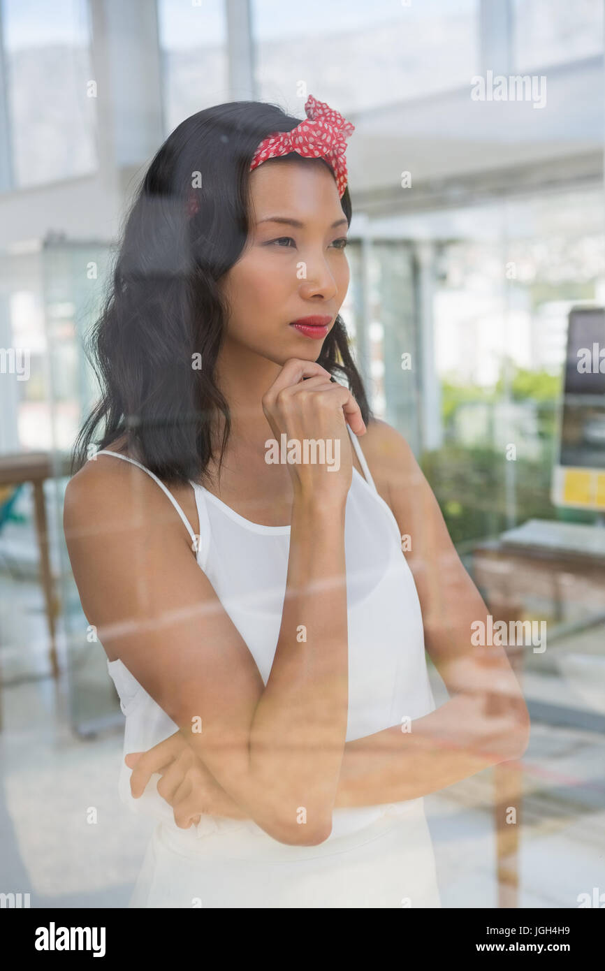 Thoughtful businesswoman looking through window at office seen through glass - Stock Image