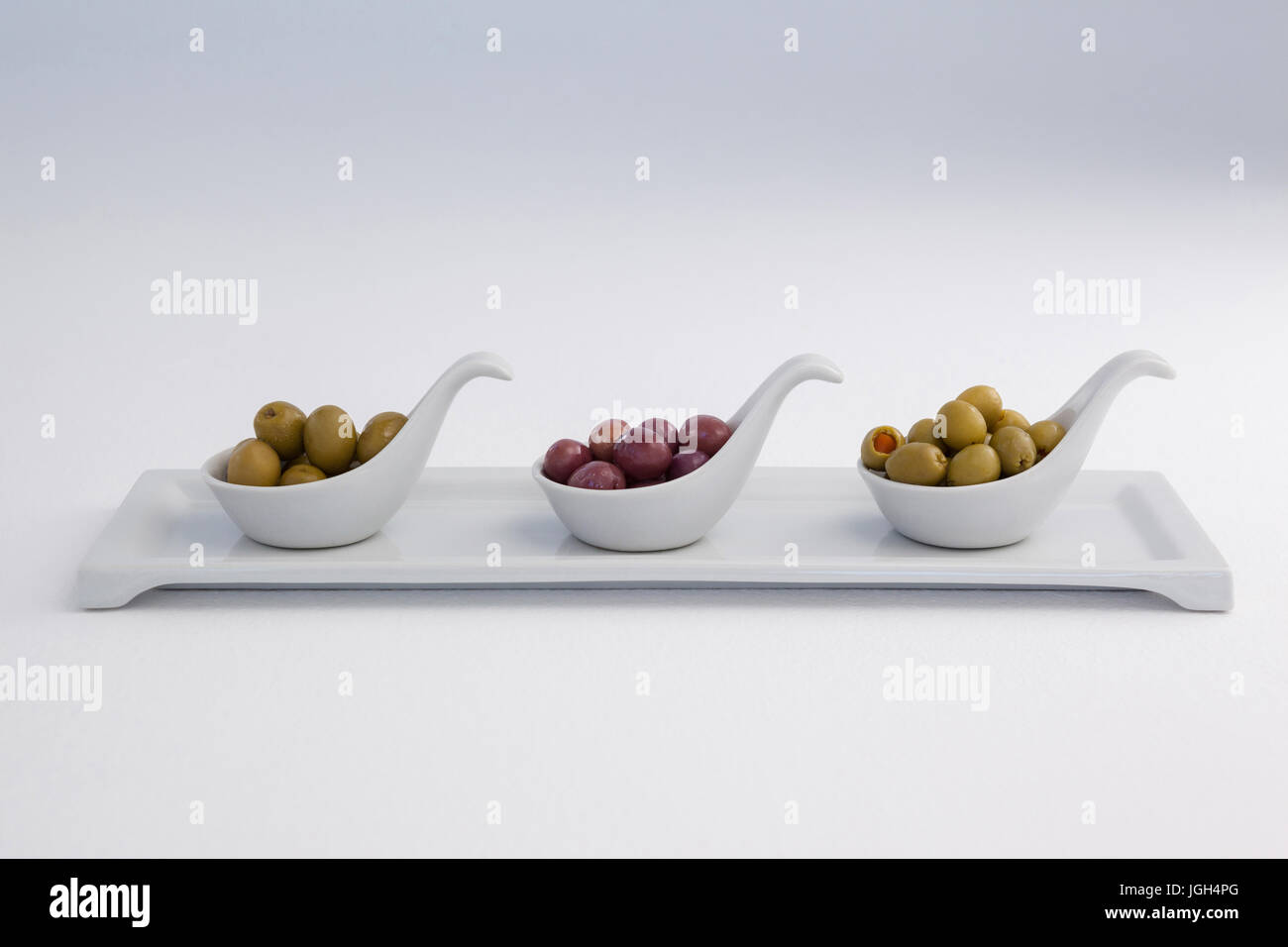Various olives in container on tray against white background - Stock Image