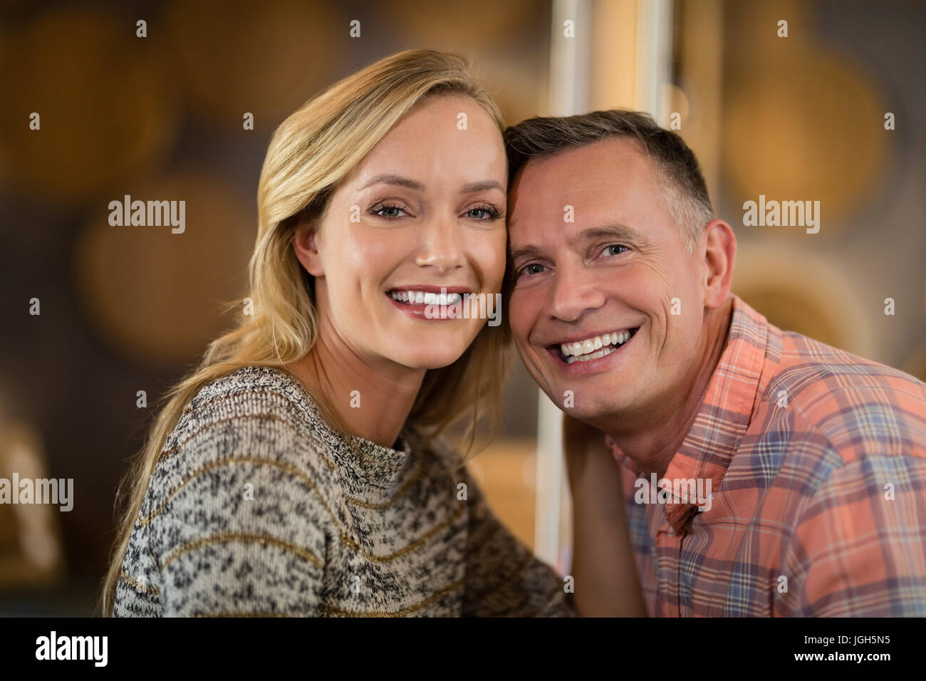 Smiling couple looking at camera in bar - Stock Image